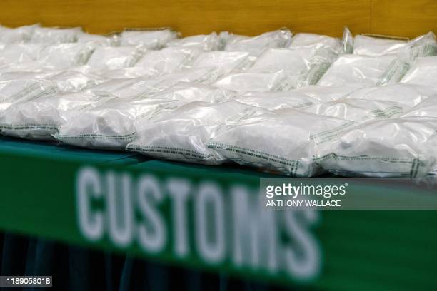 Packs of methamphetamine crystals are displayed behind a cordon during a press conference at the Customs Headquarters Building in Hong Kong on...