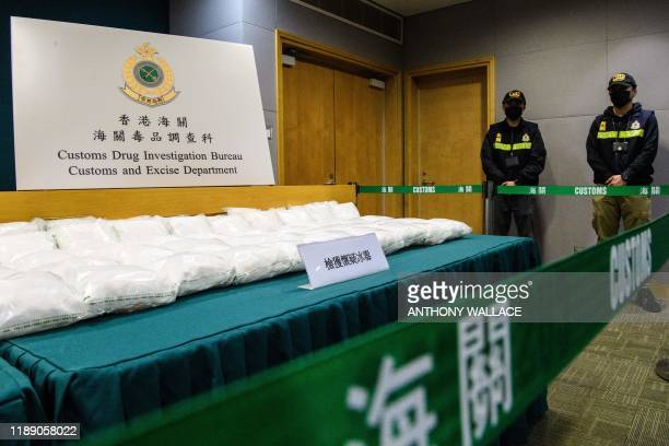 Packs of methamphetamine crystals are displayed behind a cordon as Customs Drug Investigation Bureau officers stand guard, during a press conference...