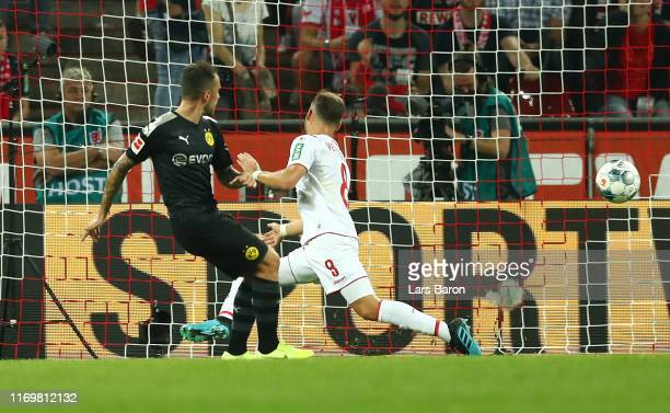 Paco Alcacer of Borussia Dortmund scores his side's third goal past Simon Terodde of 1 FC Koeln during the Bundesliga match between 1 FC Koeln and...