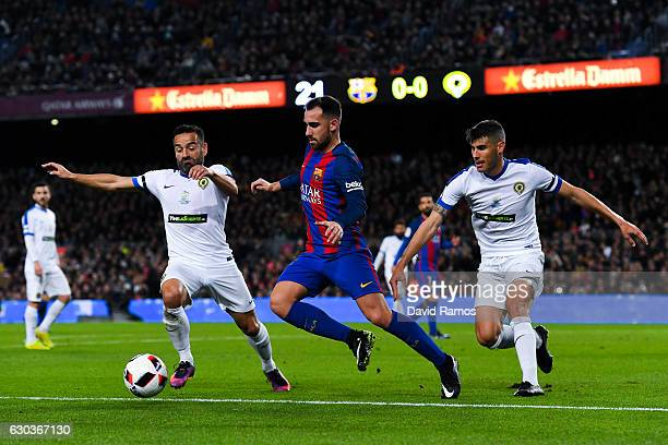 Paco Alcacer of FC Barcelona competes for the ball with Fernando and Pol Bueso of Huesca during the Copa del Rey round of 32 second leg match between...