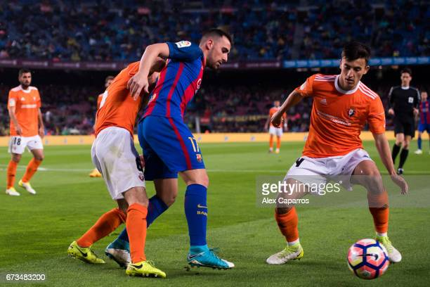 Paco Alcacer of FC Barcelona competes for the ball with Oier Sanjurjo and Aitor Bunuel of CA Osasuna during the La Liga match between FC Barcelona...