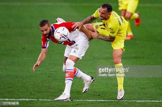Paco Alcacer of Villarreal is tackled by Victor Laguardia of Deportivo Alaves during the La Liga Santander match between Villarreal CF and Deportivo...