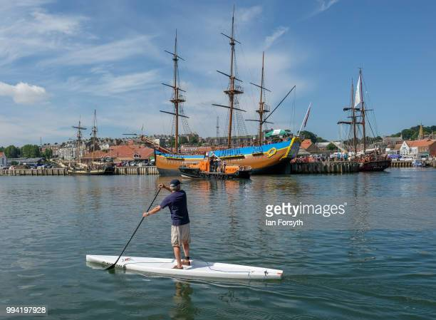 A paddle boarder moves past HMS Pickles HM Bark Endeavour and the tall ship Atyla as they are moored in the harbour during the first day of the...