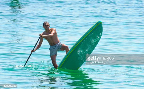 Paddle boarder performing tricks was among holiday makers who gathered to enjoy the sun on Gyllyngvase Beach on July 17, 2021 in Falmouth, United...