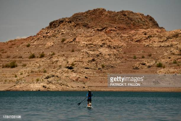 Paddle boarder rides with a dog during low water levels due to the western drought on July 20, 2021 at the Lake Mead Marina on the Colorado River in...