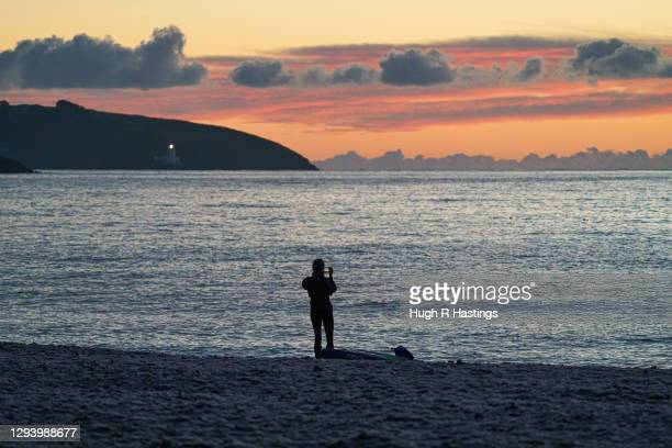 Paddle boarder takes photos of the first sunrise of the year at Gyllyngvase Beach on January 1, 2021 in Falmouth, United Kingdom. January 1st 2021...