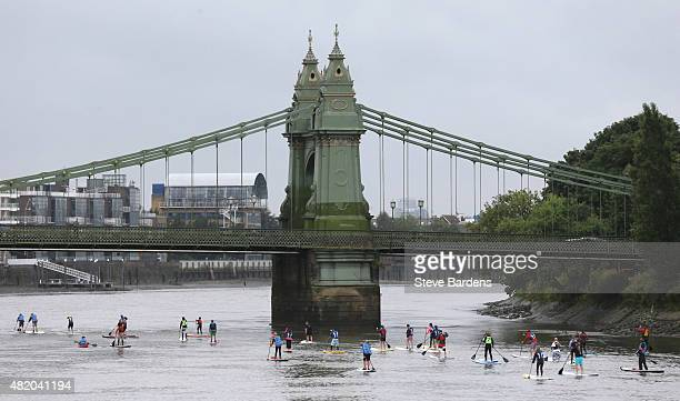 Paddle boarders approach Hammersmith bridge as they participate in the Laureus Stand up for good Thames Challenge on the river Thames on July 26 2015...