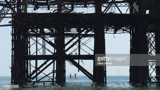 Paddle boarders make their way around the derelict West Pier on Brighton beach on May 21 2020 in Brighton England This week temperatures reached 28...