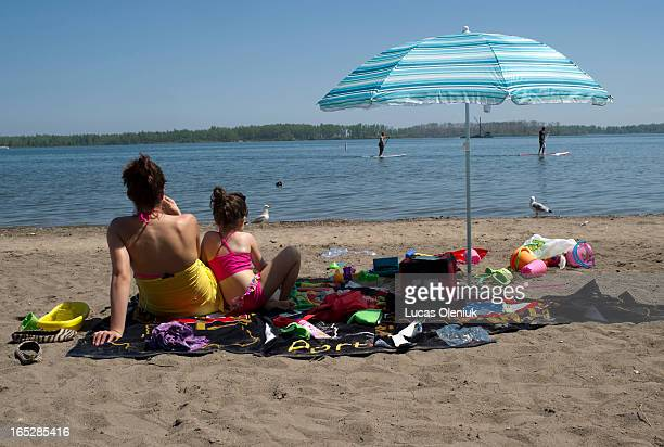 Paddle boarders passed by on Lake Ontario as Sofia Martins and her 5-year-old daughter Vanessa sat on Cherry beach eating cherries and feeding birds....