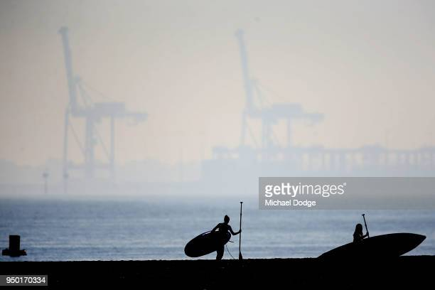 A Paddle boarders prepare on the StKilda foreshore on April 23 2018 in Melbourne Australia Melbourne has been experiencing unseasonably warm weather...