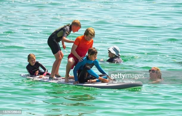 Paddle boarders were among those who gathered to enjoy the sun on Gyllyngvase Beach on July 17, 2021 in Falmouth, United Kingdom. A heat related...