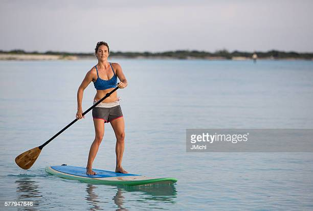 Paddle Boarding Woman on a Calm Ocean Bay.