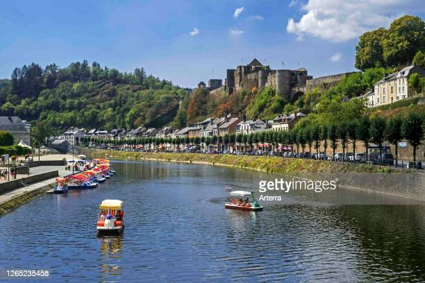 Paddle boats with tourists on the Semois river in front of Chateau de Bouillon Castle in summer, Luxembourg Province, Belgian Ardennes, Belgium.