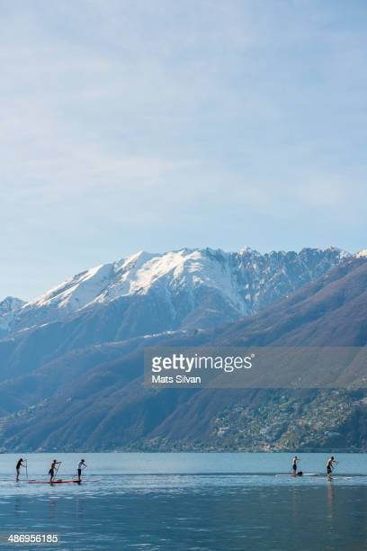 Paddleboard on an alpine lake Maggiore with snowcapped mountains in Ticino Switzerland