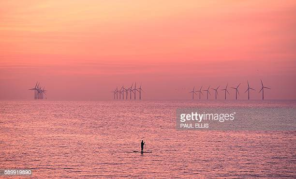 TOPSHOT A paddleboarder is pictured on the water near Leasowe at Liverpool Bay in the Irish Sea at sunset on August 15 2016 / AFP / PAUL ELLIS