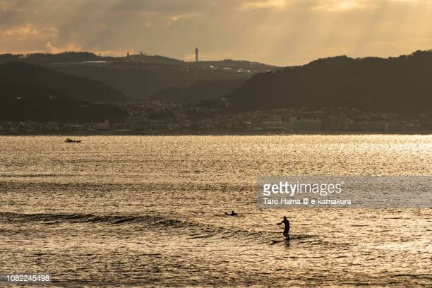 Paddleboarder riding on small wave and morning sunbeam on the beach and mountain in Kamakura and Yokosuka cities and Hayama town in Kanagawa prefecture in Japan