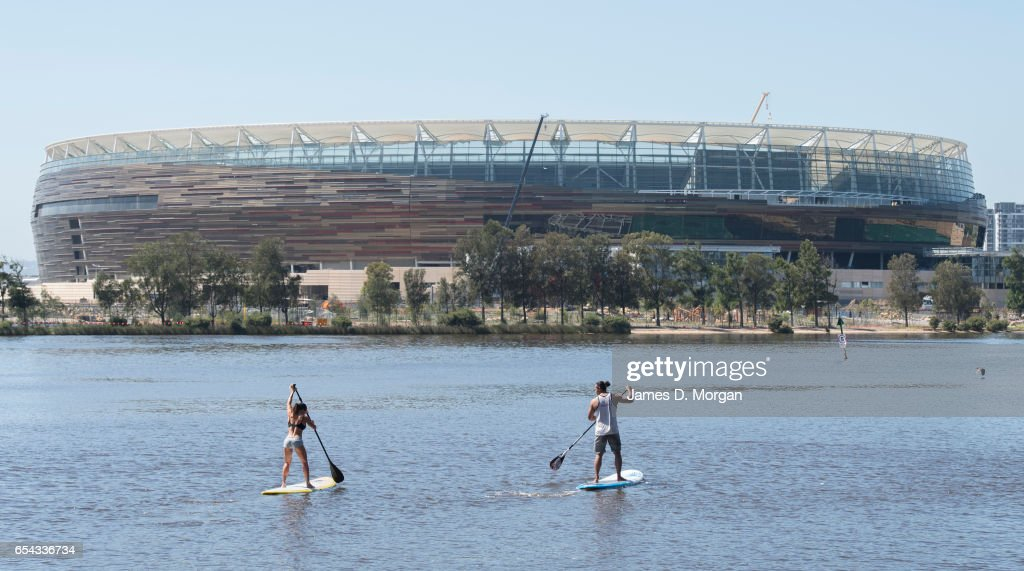 Paddleboarders on the Swan River beside the new Perth Stadium on March 17, 2017 in Perth, Australia. The WA Labor Party announced plans to sell off the naming rights of Perth Stadium and Perth Arena in order to boost the State's budget. The new stadium is currently under construction in the Perth suburb of Burswood.