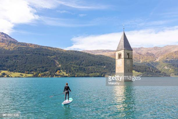 Paddleboarding near steeple and bell tower of a church sunken in Lake Reschen, Reschensee or Lago di Resia, South Tyrol, Italy