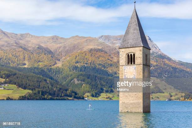 paddleboarding near steeple and bell tower of a church sunken in lake reschen, reschensee or lago di resia, south tyrol, italy - alto adige italy stock pictures, royalty-free photos & images