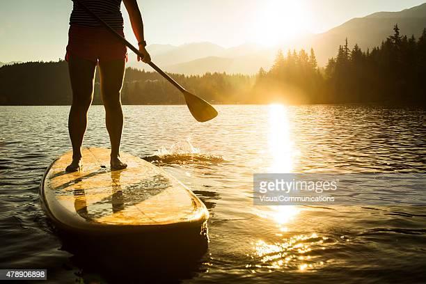paddleboarding on lake during sunrise or sunset. - paddleboard stock pictures, royalty-free photos & images