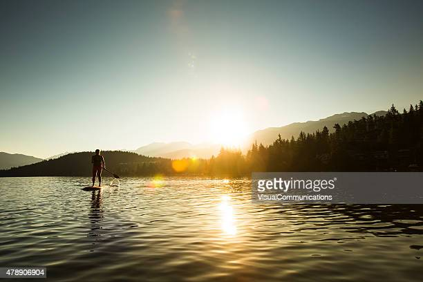 paddleboarding on lake during sunrise or sunset. - whistler british columbia stock pictures, royalty-free photos & images