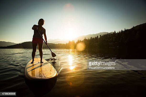 Surf de remo en el lago durante el amanecer y la puesta de sol.