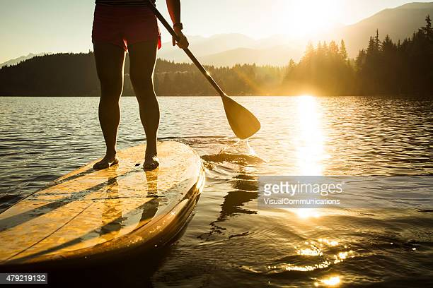 Paddleboarding on lake during sunrise or sunset.