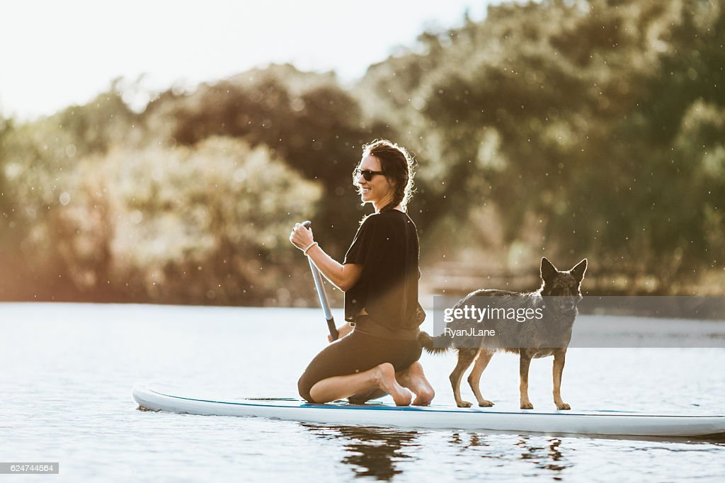 Paddleboarding Woman With Dog : Stock-Foto