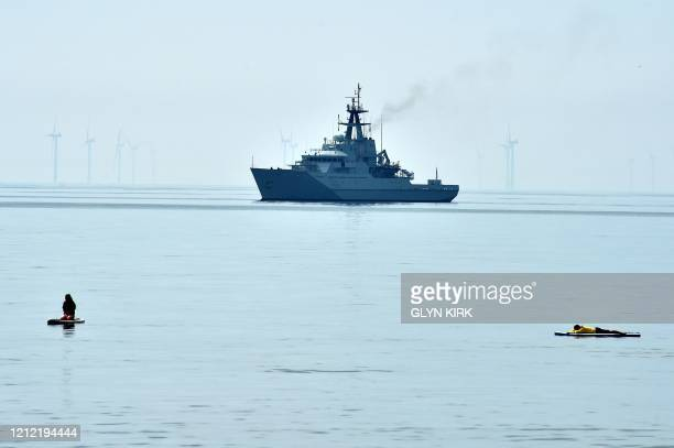 Paddlers enjoy the warm weather as HMS Severn, an offshore patrol vessel of the British Royal Navy, is anchored off the West Pier in Brighton on May...