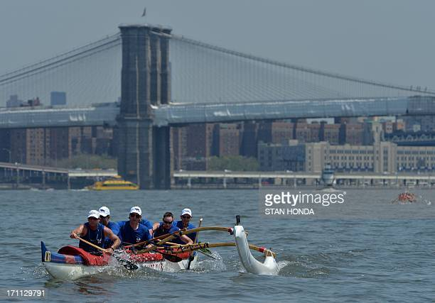 Paddlers from the Washington Canoe Club in an outrigger canoe pass the Brooklyn Bridge during the Hawaiian Airlines Liberty Challenge race June 22...