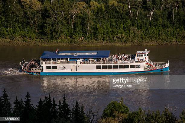 A paddlewheel riverboat moves up the Saskatchewan River on June 24 2013 in Edmonton Alberta Canada Edmonton along with its neighbor to the south...