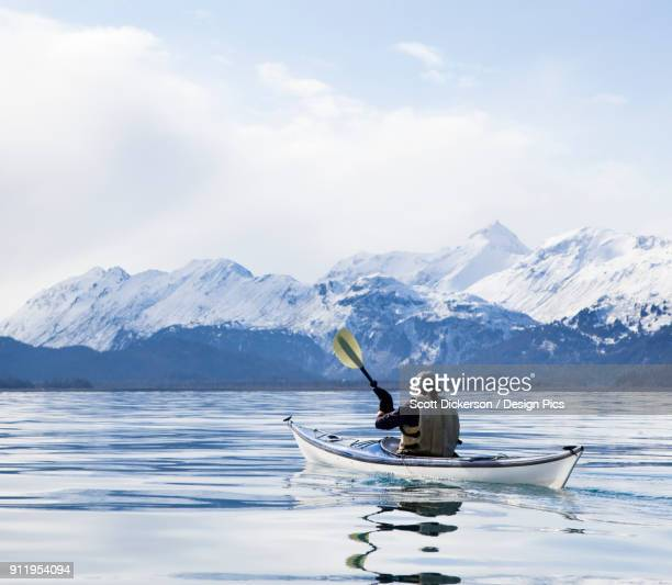 paddling in a canoe on tranquil water with a view of the snow capped kenai mountains, kachemak bay state park - kachemak bay stock pictures, royalty-free photos & images