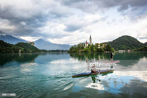 paddling to the iconic church on the lake. - slovenia stock pictures, royalty-free photos & images