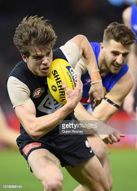 Paddy Dow of the Blues breaks free of a tackle by Marcus Bontempelli of the Bulldogs during the round 22 AFL match between the Carlton Blues and the...