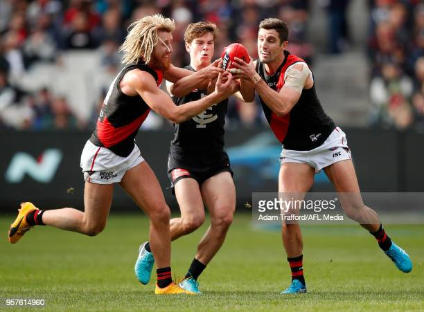 Paddy Dow of the Blues competes for the ball with Dyson Heppell and David Myers of the Bombers during the 2018 AFL round eight match between the...