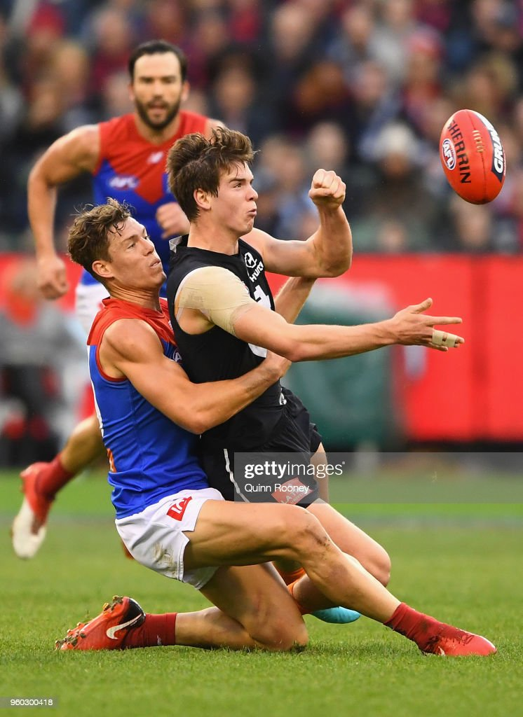 Paddy Dow of the Blues handballs whilst being tackled by Jake Melksham of the Demons during the round nine AFL match between the Carlton Blues and the Melbourne Demons at Melbourne Cricket Ground on May 20, 2018 in Melbourne, Australia.