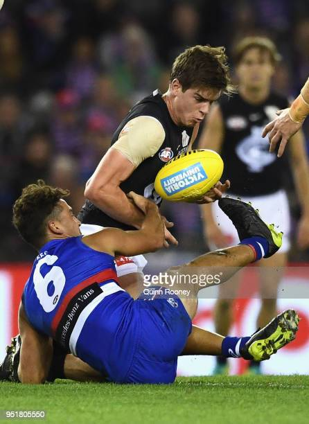 Paddy Dow of the Blues handballs whilst being tackled by Luke Dahlhaus of the Bulldogs during the AFL round six match between the Western Bulldogs...