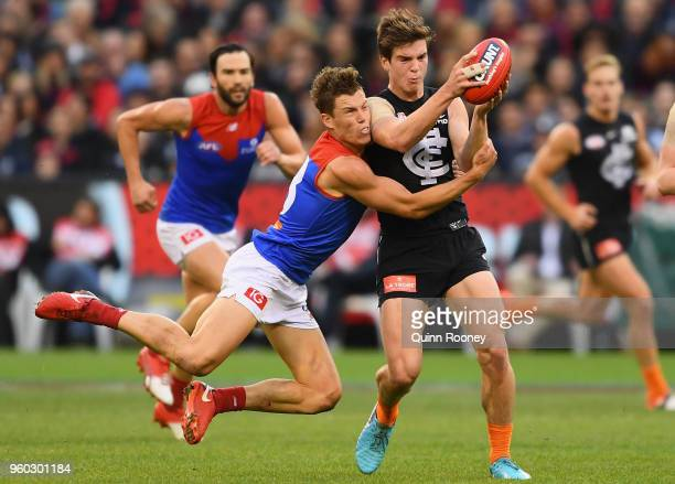 Paddy Dow of the Blues is tackled by Jake Melksham of the Demons during the round nine AFL match between the Carlton Blues and the Melbourne Demons...