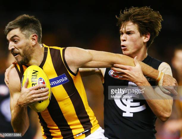 Paddy Dow of the Blues tackles Ricky Henderson of the Hawks during the round 18 AFL match between the Carlton Blues and the Hawthorn Hawks at Etihad...