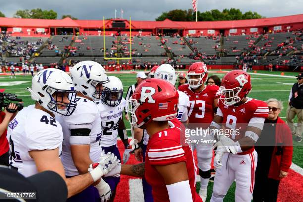 Paddy Fisher of the Northwestern Wildcats and Isaiah Wharton of the Rutgers Scarlet Knights shake hands with other team captains at the coin toss...