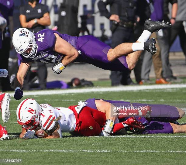 Paddy Fisher of the Northwestern Wildcats flies over Wan'Dale Robinson of the Nebraska Cornhuskers after teammate Chris Bergin brings down Robinson...