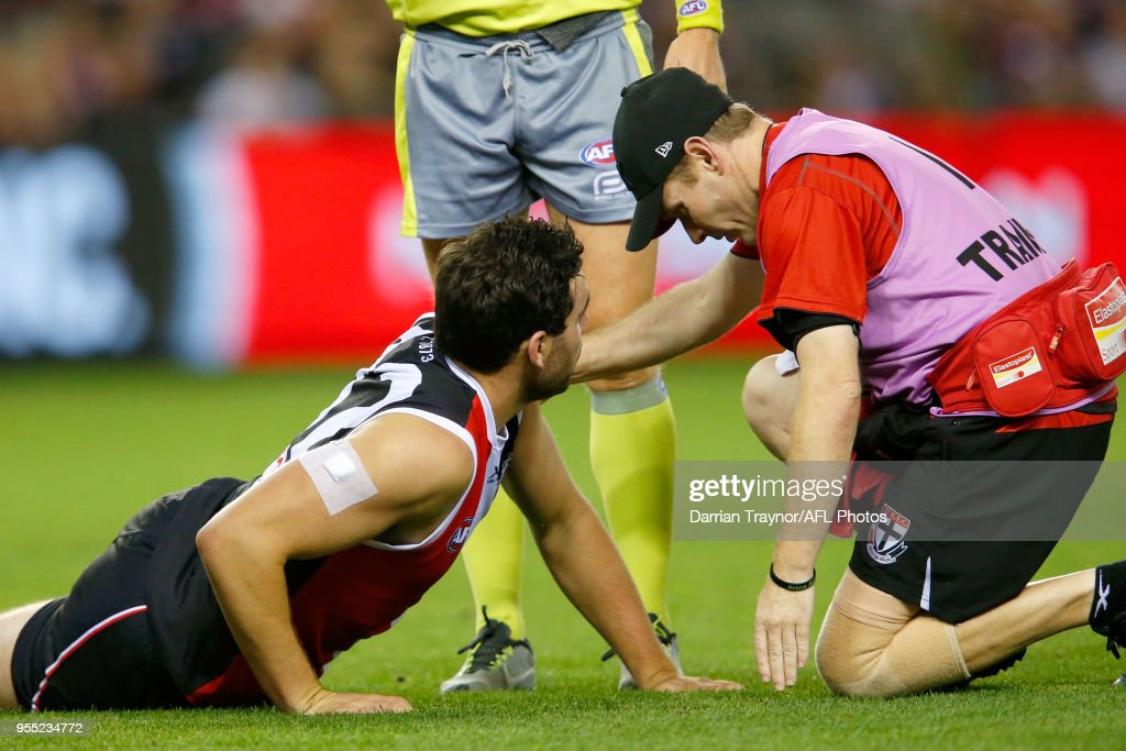 Paddy McCartin of the Saints is helped by a trainer after colliding with Neville Jetta of the Demons during the round seven AFL match between St Kilda Saints and the Melbourne Demons at Etihad Stadium on May 6, 2018 in Melbourne, Australia.