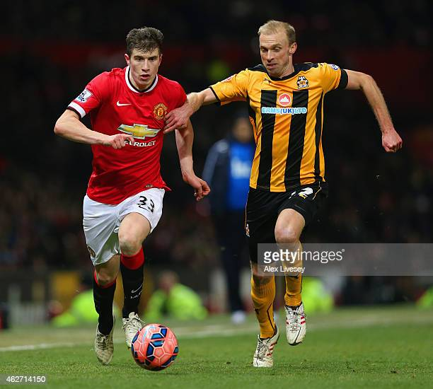 Paddy McNair of Manchester United and Luke Chadwick of Cambridge United battle for the ball during the FA Cup Fourth round replay match between...