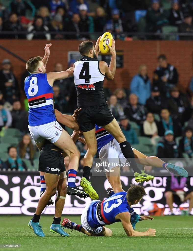 Paddy Ryder of Port Adelaide marks over Josh Schache and Jackson Trengove of the Bulldogs during the round 13 AFL match between Port Adelaide Power and the Western Bulldogs at Adelaide Oval on June 14, 2018 in Adelaide, Australia.