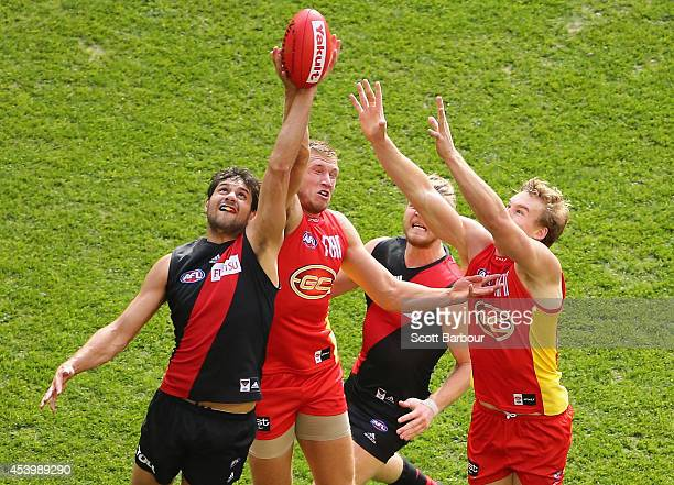 Paddy Ryder of the Bombers and Sam Day of the Suns compete for the ball during the round 22 AFL match between the Essendon Bombers and the Gold Coast...