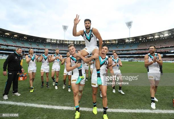 Paddy Ryder of the Power is chaired off by teammates after playing his 200th match during the round 14 AFL match between the Collingwood Magpies and...