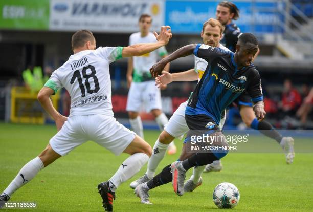 Paderborn's German midfielder Christopher AntwiAdjei and Moenchengladbach's Austrian defender Stefan Lainer vie for the ball during the German first...