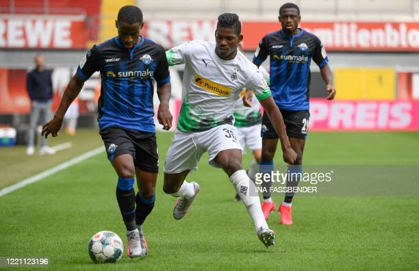 Paderborn's German midfielder Christopher AntwiAdjei and Moenchengladbach's German midfielder Florian Neuhaus vie for the ball during the German...