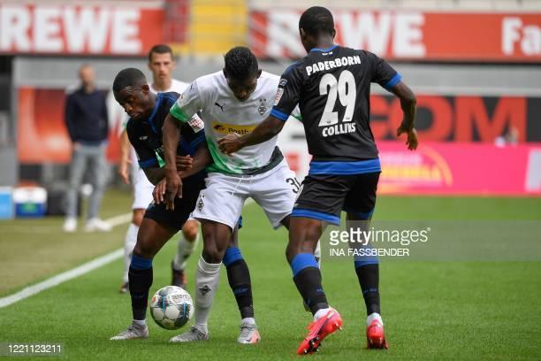 Paderborn's German midfielder Christopher AntwiAdjei Paderborn's Nigerian defender Jamillu Collins and Moenchengladbach's German midfielder Florian...