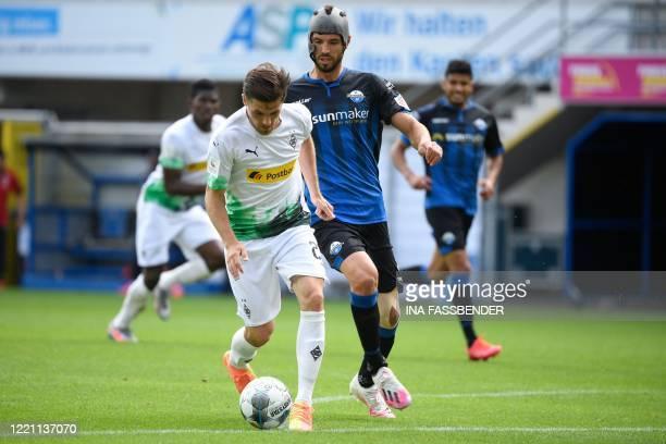 Paderborn's German midfielder Klaus Gjasula and Moenchengladbach's German midfielder Jonas Hofmann vie for the ball during the German first division...